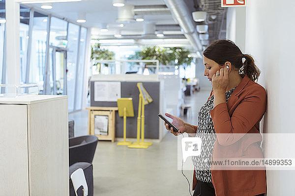 Schwangere Geschäftsfrau  die am Arbeitsplatz mit einem Smartphone Musik hört