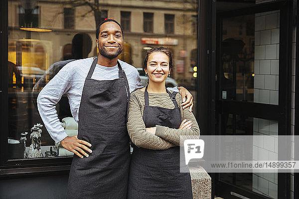 Porträt selbstbewusster junger Besitzer vor Feinkost-Fenster in der Stadt