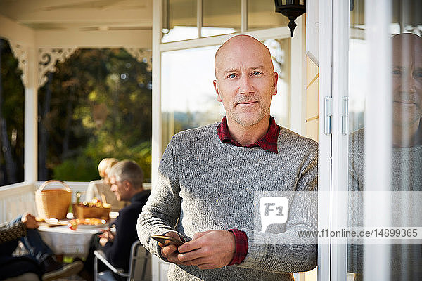 Portrait of confident bald mature man standing on porch with friends in background
