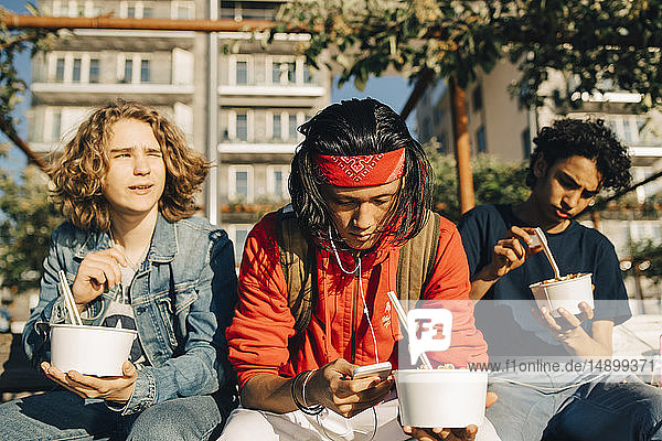 Young man using mobile phone while friends eating take out food in city during sunny day