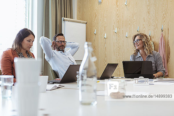 Business colleagues using laptops while sitting at conference table in board room