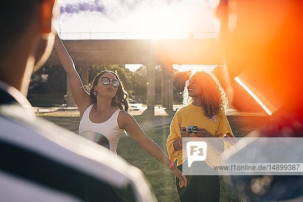 Verspielte Frau amüsiert sich mit Freunden während eines Musikfestivals an einem sonnigen Tag