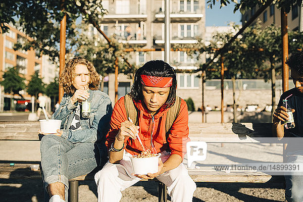 Friends eating meal from containers while sitting on bench in city during sunny day