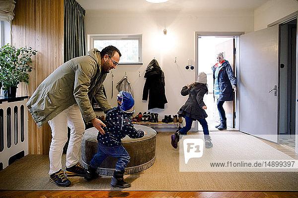 Verspielte Geschwister mit den Eltern im Matschraum zu Hause