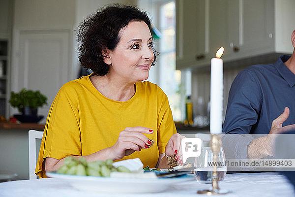 Lächelnde reife Frau schaut weg  während sie bei einem Freund am Esstisch sitzt