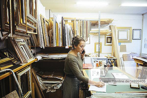 Selbstbewusste junge Handwerkerin spricht mit einem Smartphone  während sie an der Werkbank im Einrahmungsgeschäft mit Papier schreibt