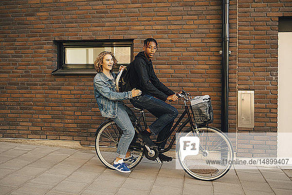 Portrait of teenage boy riding bicycle with friend on street in city