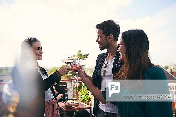 Lächelnde Freunde stoßen bei einer Party auf der Terrasse auf Getränke an