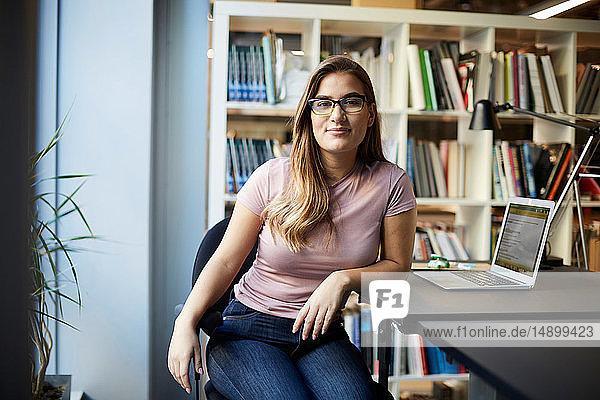 Porträt einer selbstbewussten jungen Geschäftsfrau  die in einem kreativen Büro am Schreibtisch sitzt