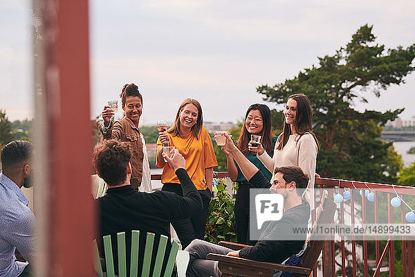 Happy friends toasting drinks on terrace during party