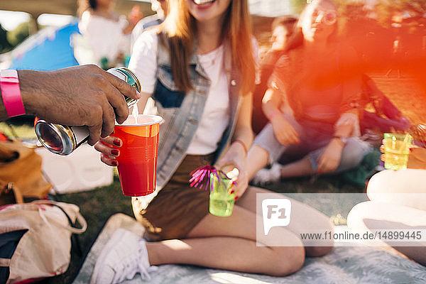 Ausgeschnittenes Bild eines Mannes  der auf einer Party auf einem Fest Alkohol in das Glas eines Freundes gießt Ausgeschnittenes Bild eines Mannes, der auf einer Party auf einem Fest Alkohol in das Glas eines Freundes gießt