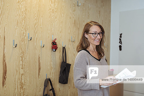 Smiling confident businesswoman holding documents while standing at office
