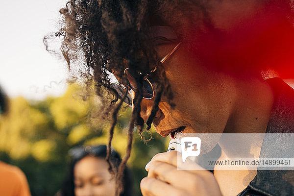 Nahaufnahme eines jungen Mannes mit lockigem Haar  der durch eine elektronische Zigarette raucht