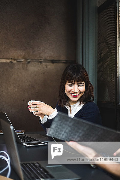 Smiling female entrepreneur holding coffee cup discussing with colleague over document at desk in office