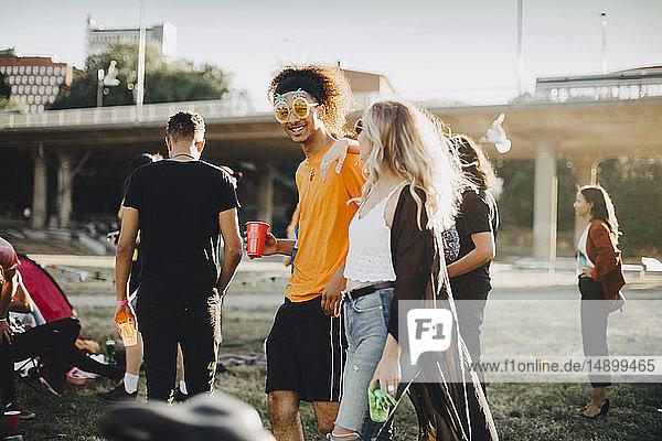 Lächelnder Mann und Frau im Gespräch mit Freunden im Hintergrund