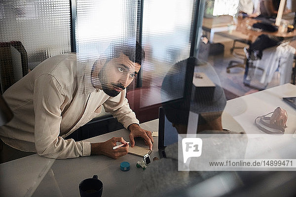 Businessman writing in note pad while discussing with male colleague at desk in creative office