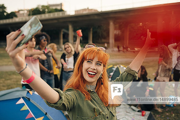 Fröhliche junge Frau  die während eines Musikfestivals mit Freunden beim Zelten Selbsthilfe betreibt