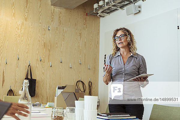 Confident mature businesswoman with digital tablet discussing in meeting
