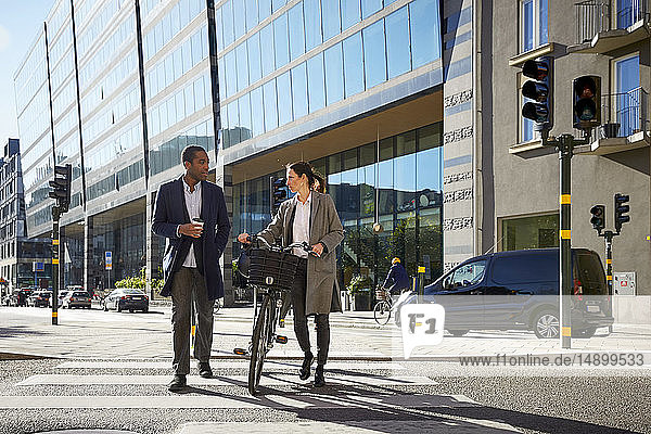 Frau und Mann unterhalten sich in voller Länge beim Gehen mit dem Elektrofahrrad auf dem Zebrastreifen gegen Gebäude in der Stadt