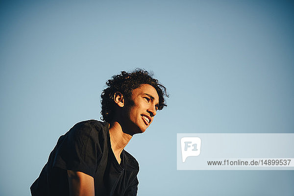 Low angle view of smiling teenage boy looking away against clear blue sky during sunset