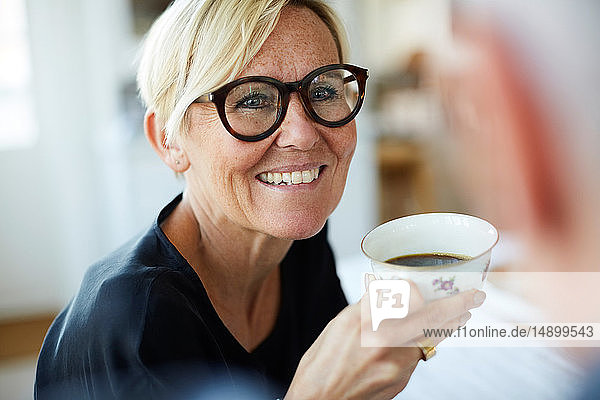 Smiling mature woman holding coffee cup while looking away at home