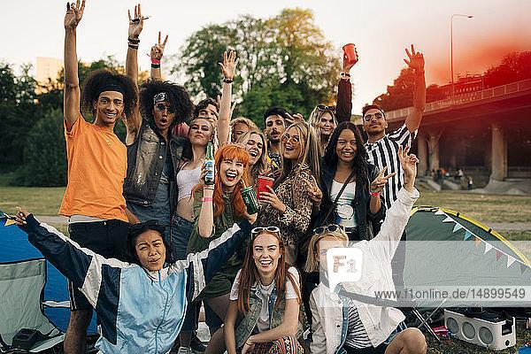 Porträt von fröhlichen jungen Freunden  die während des Festivals zelten