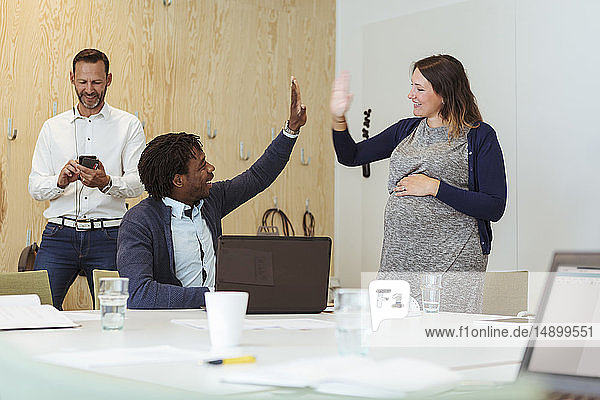 Happy multi-ethnic coworkers giving high-five to each other at conference table