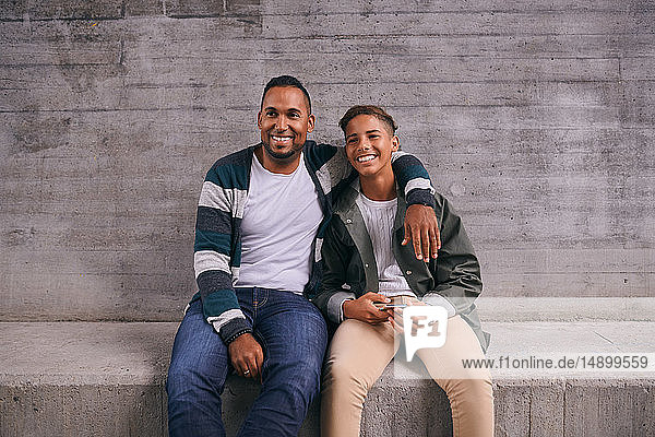 Cheerful father and son looking away while sitting against wall