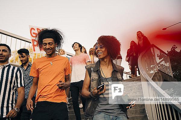 Lächelnde Freunde mit Spruchband sprechen  während sie auf Stufen gegen den Himmel gehen