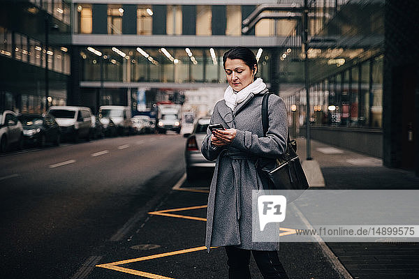Businesswoman using smart phone while standing on city street against building