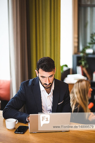 Confident male entrepreneur using laptop while sitting at table in office