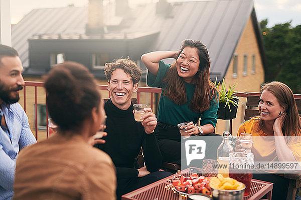 Fröhliche Freunde unterhalten sich bei geselligem Beisammensein auf der Terrasse