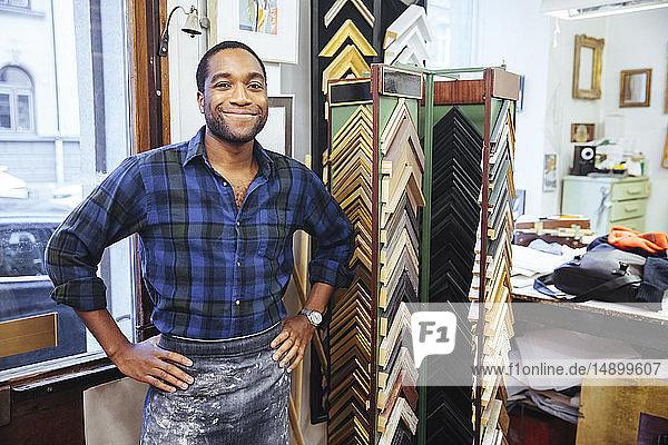 Porträt eines lächelnden jungen Handwerkers  der mit den Händen auf der Hüfte in einer Rahmenwerkstatt steht