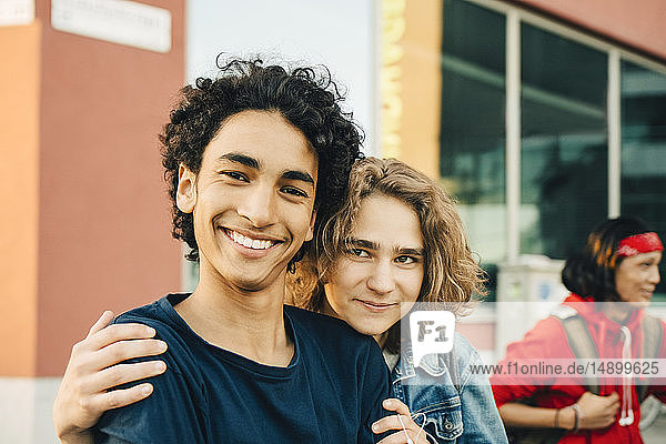 Portrait of smiling teenage boy with friend in city