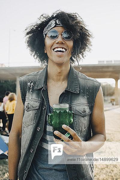 Porträt eines lächelnden jungen Mannes mit Krug in Musikveranstaltung