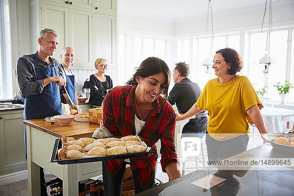 Happy friends preparing food together in kitchen at home