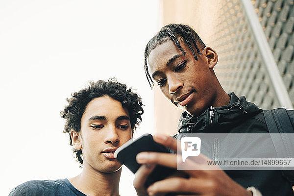 Niedrigwinkelansicht eines Teenagers  der einem Freund in der Stadt ein Handy zeigt