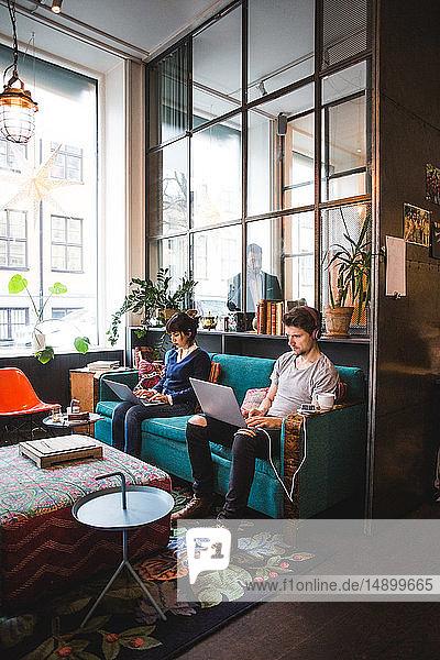 Selbstbewusste multiethnische männliche und weibliche Berufstätige mit Laptops  die im Büro auf dem Sofa sitzen