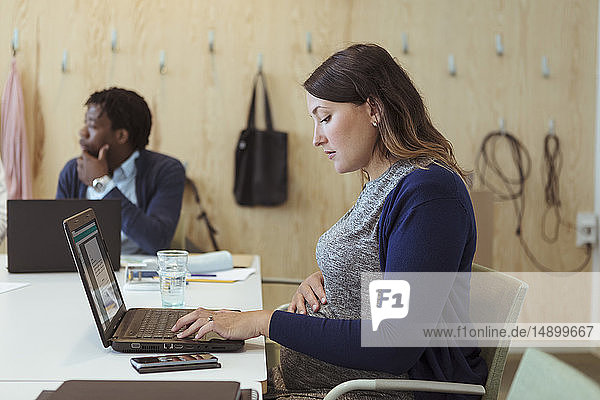 Side view of pregnant businesswoman using laptop at conference table in office
