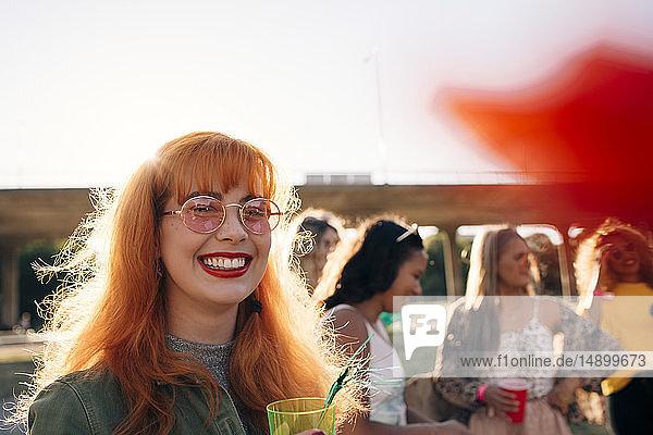 Lächelnde junge Frau trinkt während eines Konzerts mit Freunden