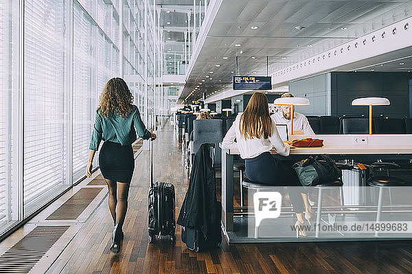 Full length rear view of businesswoman walking with luggage by colleagues waiting at airport departure area