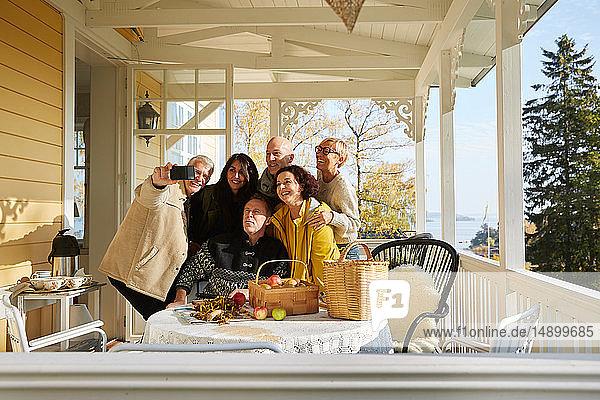 Glückliche reife Freunde posieren für Handy-Selfie auf der Veranda