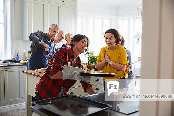 Excited woman looking at friend baking in kitchen at home