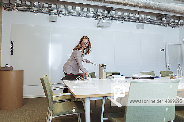 Mid adult businesswoman working at conference table in board room