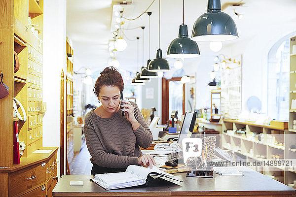 Junge Verkäuferin telefoniert am Handy  während sie im Baumarkt eine Akte ansieht