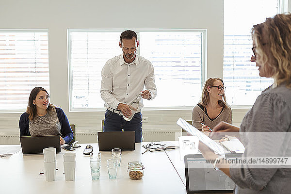 Businessman drinking water while colleagues discussing in meeting at office