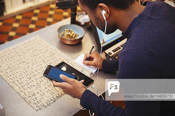 Schrägaufnahme eines jungen männlichen Besitzers  der mit einem Smartphone telefoniert  während er an der Kasse eines Möbelhauses schreibt