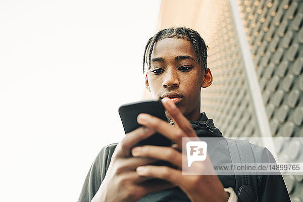 Low angle view of serious teenage boy using mobile phone in city