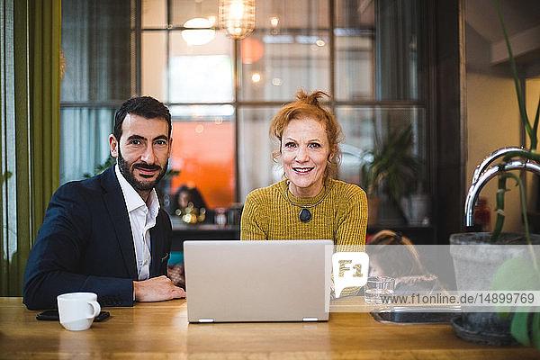 Porträt von lächelnden weiblichen und männlichen Geschäftskollegen  die mit Laptop am Tisch im Büro sitzen
