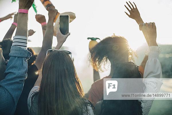 Frau hält Smartphone in der Hand  während sie mit Freunden beim Musikfestival genießt